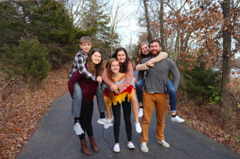 """Posing for a family portrait, senior Emily Feuerborn smiles alongside her siblings including her eldest sister Megan, who she says had """"a profound impact on her identity."""""""