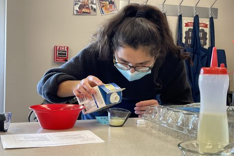 Focusing on measuring correctly, junior Leila Garcia pours milk into a measuring cup.