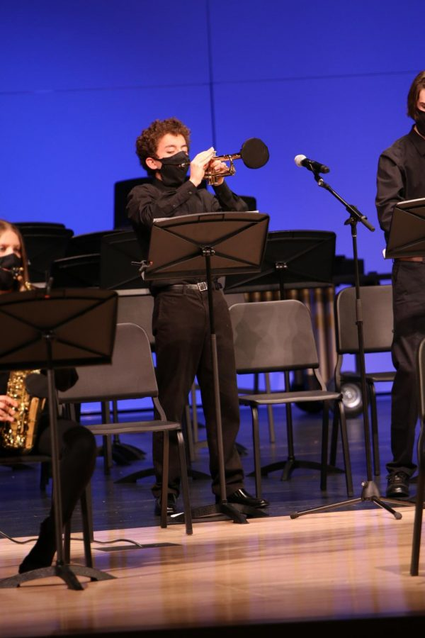 Looking down at his music, sophomore Charles Beal plays the trumpet during his solo.
