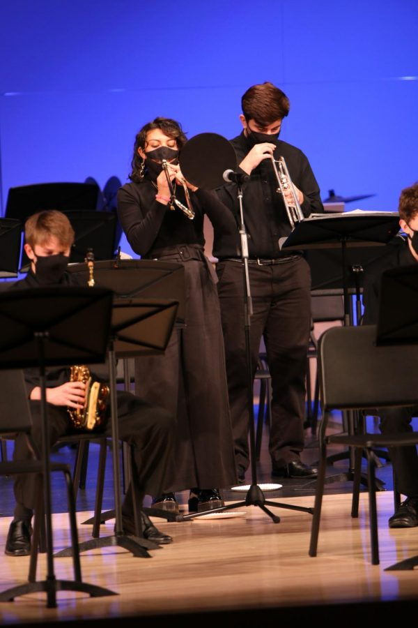 Facing the microphone, junior Olivia Franco plays the trombone during her solos with the jazz band.