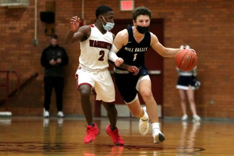 Blocking his opponent from grabbing the ball from him, senior Nick Mason dribbles the ball down the court Tuesday, March 9. The game ended with a final score of 52-47 with a victory for Washington and an end for the boys basketball team post-season.