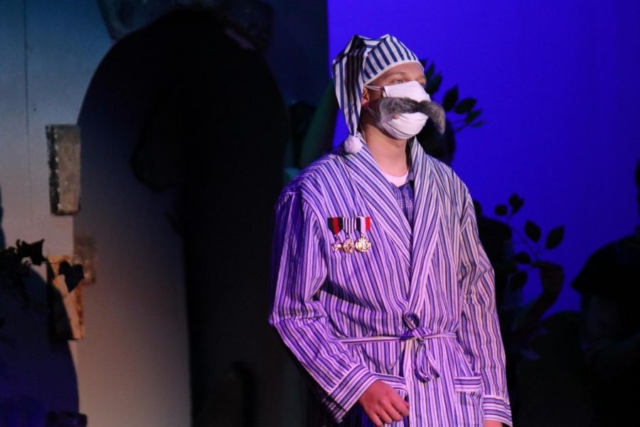 With a mustache on his mask, junior Benjamin Baumgart sings while playing the role of the Major General.
