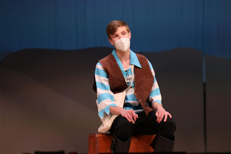 Sitting on a suitcase, senior Leif Campbell continues to sing while playing the role of Frederic.