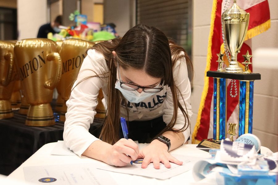 Helping out with signing letters for job olympics, junior Kinley Drummond gets ready for the award ceremony.