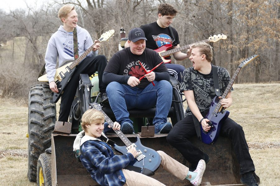 "Holding their instruments, sophomore Anthony Molinaro and his band ""Holiday Drive"" pose for a picture while sitting on a tractor during band practice Thursday, Feb. 25. The band practices most Sundays. ""The practices consist of us playing covers, our own songs and messing around,"" Molinaro said."