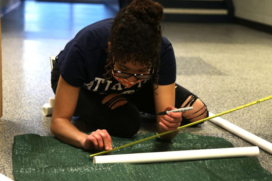Using a marker, senior Alex Owens marks the correct measurement of where she needs to cut for the dog bed's side post on the PVC pipe.