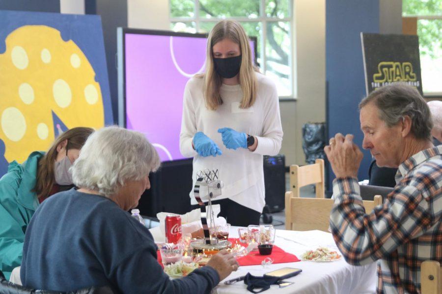 Gloves on her hands, junior Katie Schwartzkopf checks on her table.