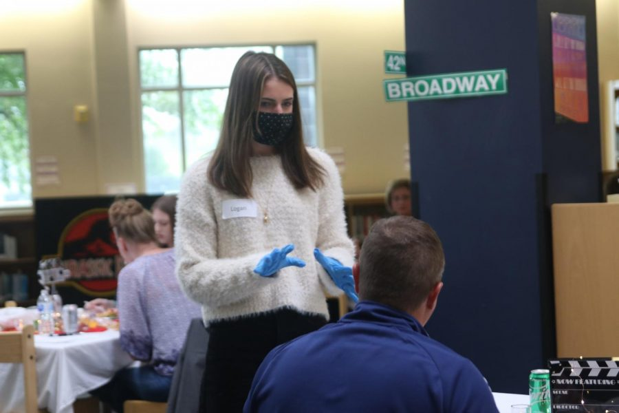 Hands up, junior Logan Pfeister listens to what her guests are saying.