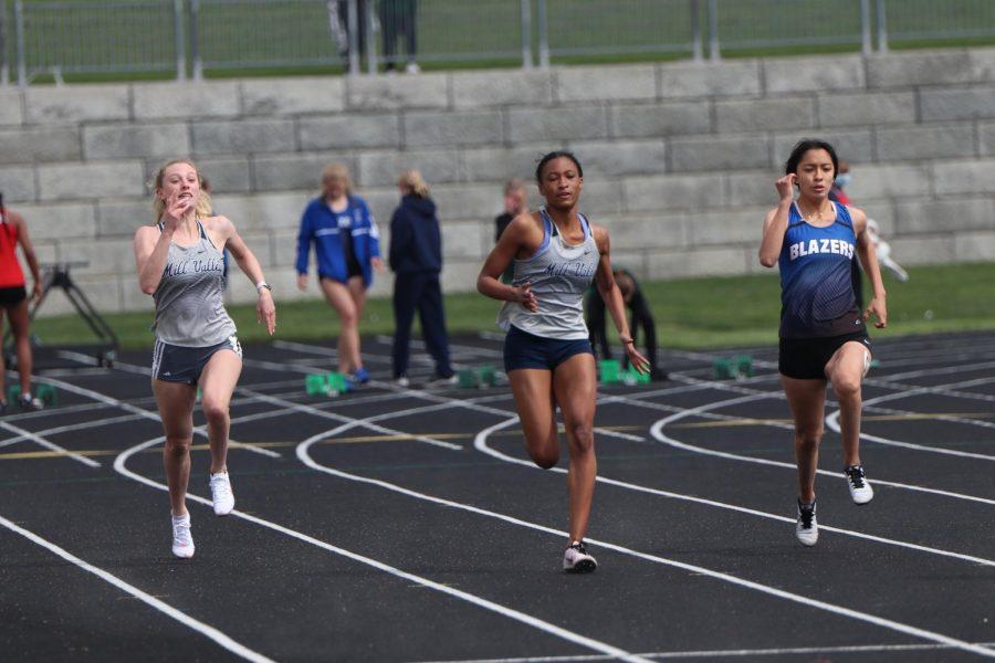 Side by side, senior Abby Drumm and sophomore Savannah Harvey race in the 100 meter dash.