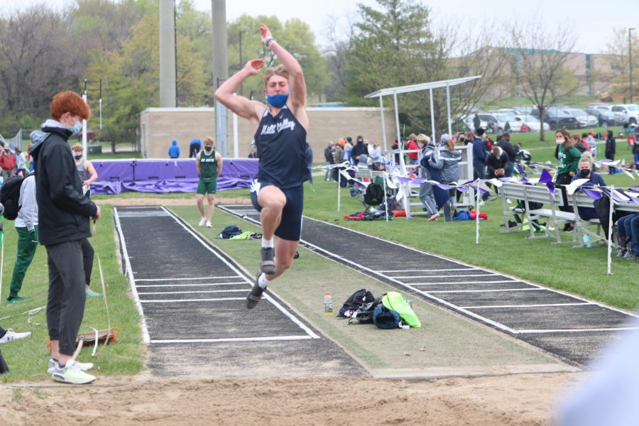 Up in the air, sophomore Hayden Jay jumps into the sand pit.