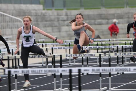 Over a hurdle, junior Quincy Hubert runs in the 100 meter hurdles. Hubert was also an event champ in the 300 meter hurdles.