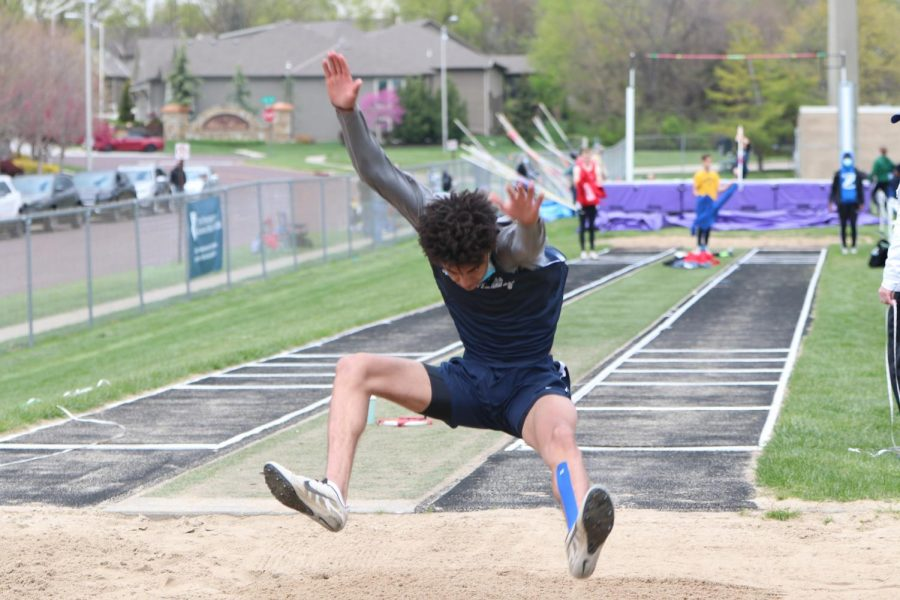 Arms up in the air, junior Adrian Dimond leaps into the sand pit.