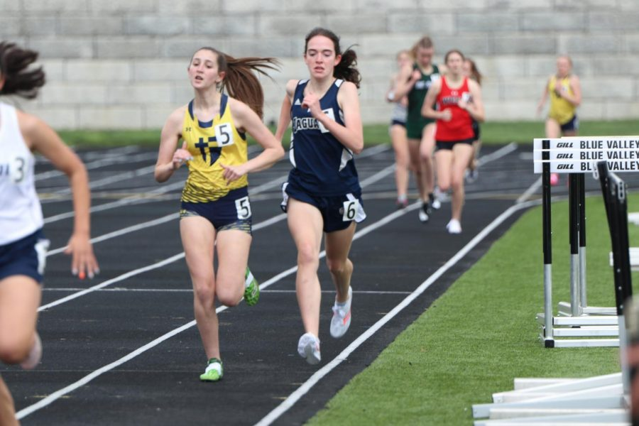 Next to a Saint Thomas Aquinas runner, sophomore Cree Crawford attempts to pass her opponent.