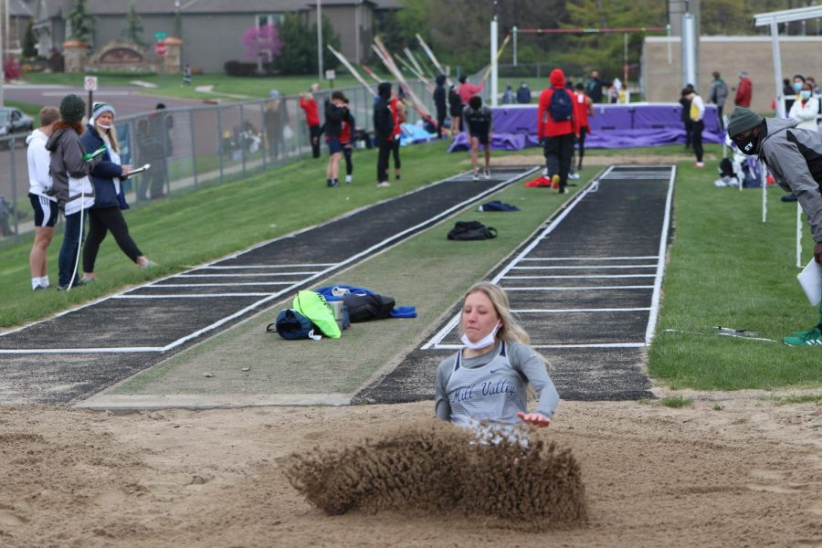 After her jump, junior Kate Roth falls into the sand pit.