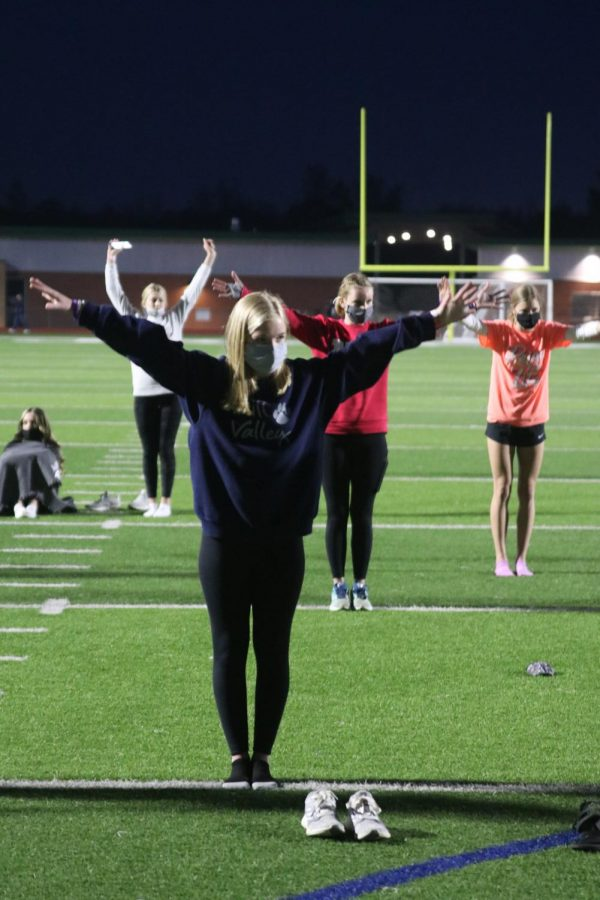 Arms raised in the air, freshman Molly Morgan stretches during yoga.