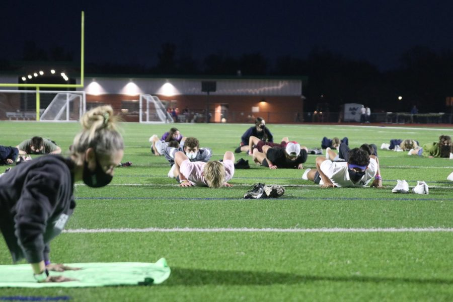 Participants lay down on the football field while listening to the yoga instructor.