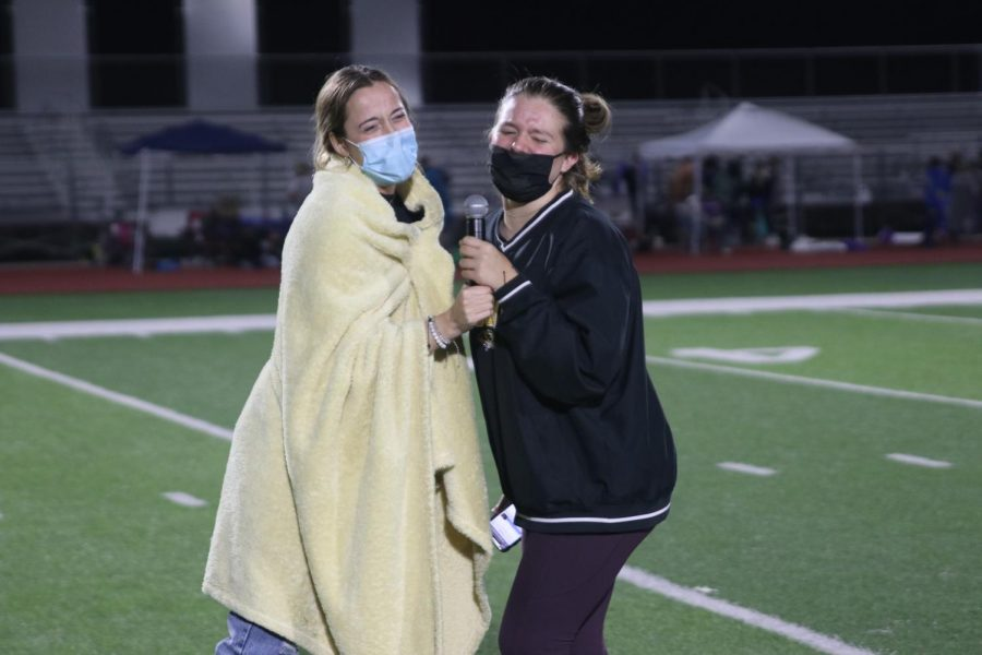"""Both holding the microphone, senior Lexi Claeys and McKenzie White sing """"Bohemian Rhapsody"""" by Queen."""