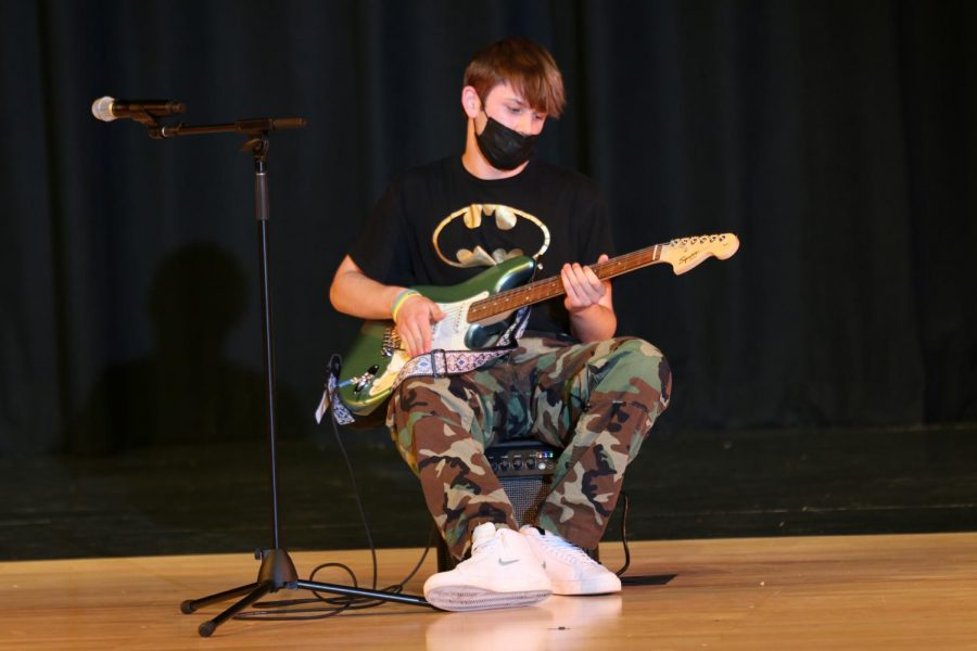 Sitting on his amp, junior Fischer Unruh plays his electric guitar during the talent portion of the pageant.