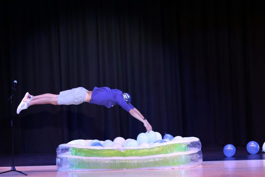 Senior Cole McClure dives into a pool of blue and white balloons to demonstrate his swimming skills during the talent portion of the pageant.