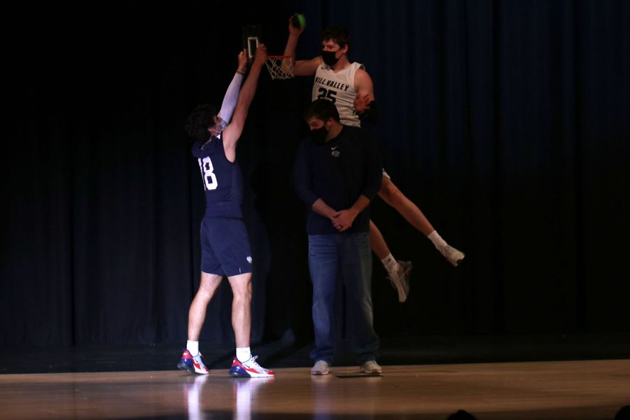 While assistant basketball coach Kurtis Bangle stands on stage, senior Aaron Kephart dunks a basketball over his head into a basket held by senior Peter Janssen.