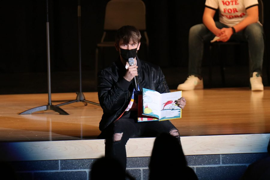 "During the poem portion of the evening, junior Fischer Unruh reads Dr. Seuss's ""One fish, two fish, red fish, blue fish"" to the crowd."