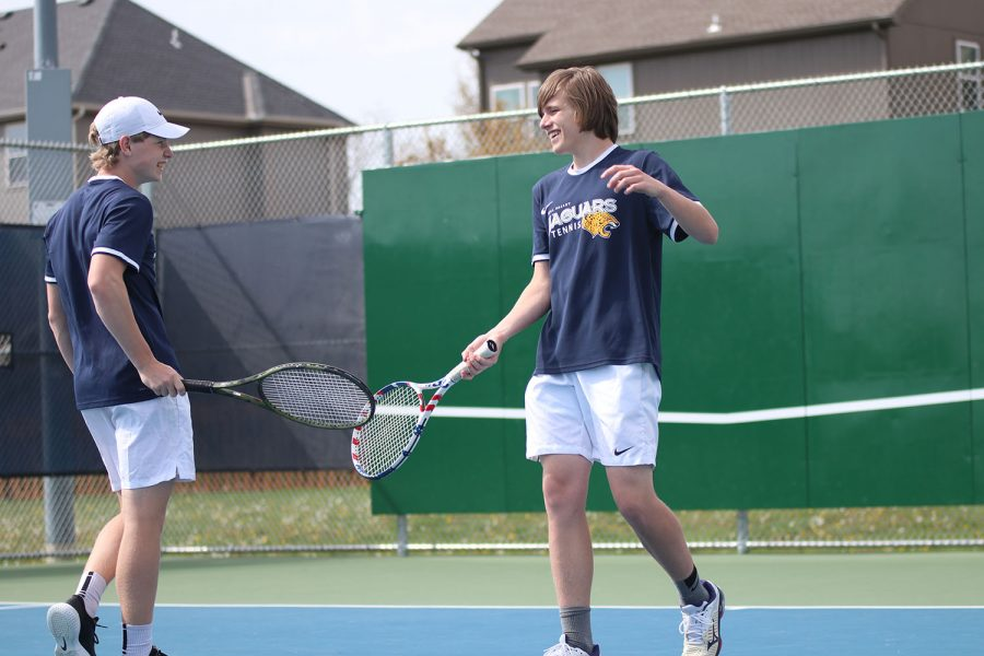 After winning a point, junior Derek Mulder celebrates with his doubles partner junior Ben Fitterer.