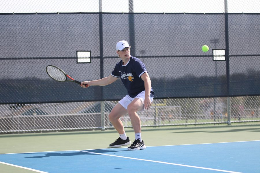 While swinging his racket back, junior Ben Fitterer follows the ball with his eyes.