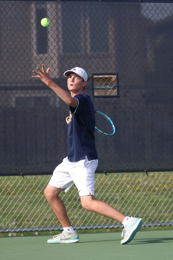 Preparing to serve the ball, junior Luke Hansen tosses it up in the air while swinging his racket back.