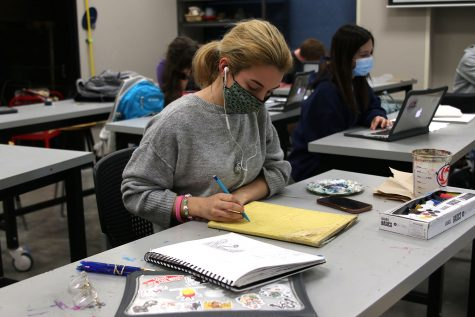 Intently gazing down at her sketchbook, junior Natalie Hernandez begins to sketch her plans for her painting on Thursday, April 8.