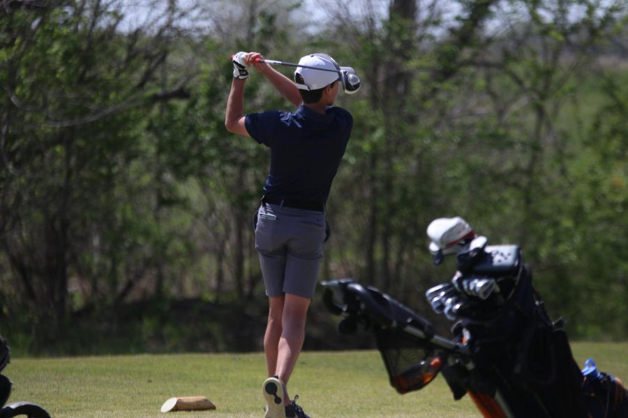 Swinging his club, sophomore Codey Geis drives his ball down the course.