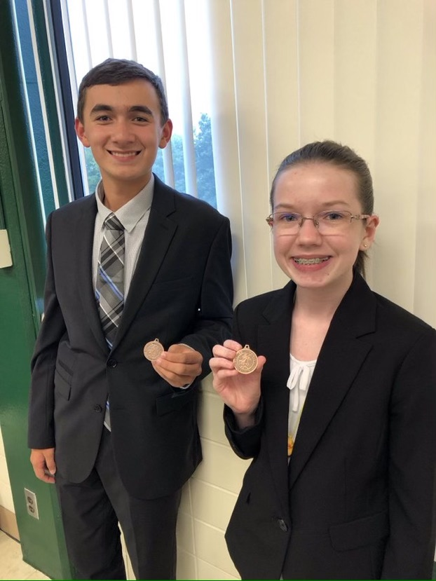 Posing with their medals, sophomores Sarah Johnston and Isaac Steiner smile with their award from a previous debate tournament Oct. 5 2019.