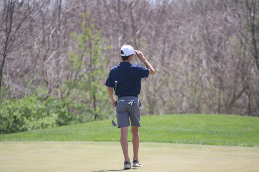 Waiting his turn to hit, sophomore Codey Geis readjusts his hat.