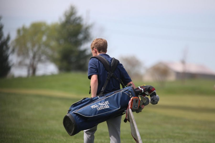 Making his way to the next hole, sophomore Matt Morgan carries his clubs.