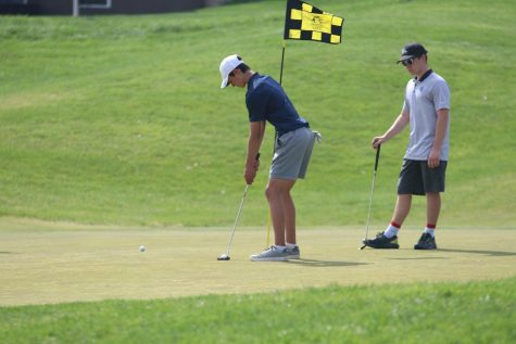 Lining up his shot, junior Brock Olson takes his turn putting.