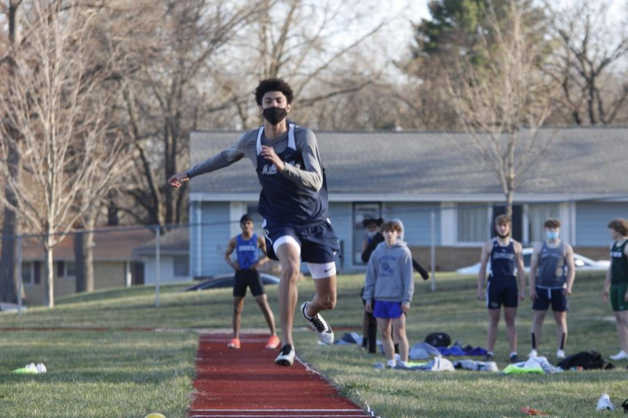 Competing in triple jump, junior Adrien Dimond throws himself into the sand pit. Dimond took 1st place with an impressive 41-09.50 mark.
