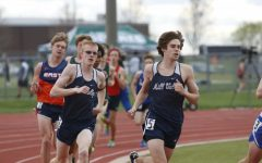 Rounding the corner of the track, senior John Lehan and junior Chase Schieber fight to maintain their places in the 1600m race. Lehan placed 8th and Schieber placed 9th.
