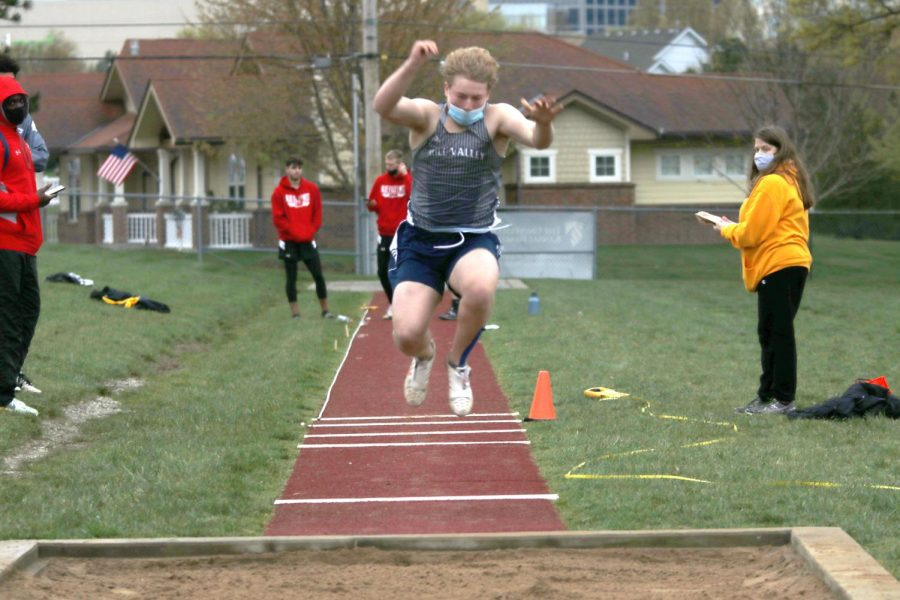In the air, sophomore Noah Coy throw himself forward as far as he can into the long jump pit.