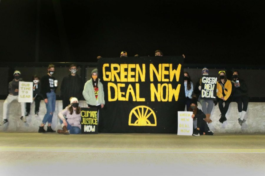 Shawnee Sunrise Chapter members pose in front of a  banner drop supporting the Green New Deal on K-7 Highway Friday, Oct. 18.