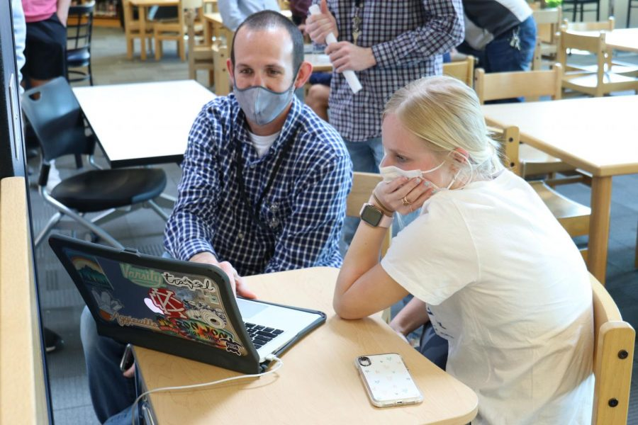 Looking at a school-issued MacBook, Director of Technology Brandon Riffle and junior Abby Steiger work to open up storage space for the macOS Big Sur update Friday, April 2.