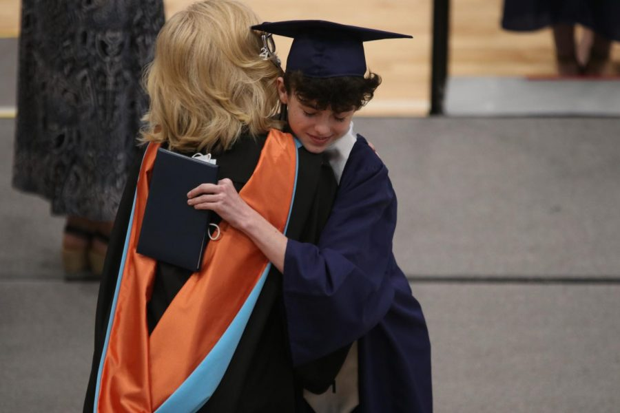 Hugging principal Gail Holder, senior Campbell Norman smiles with his diploma and mask in hand.