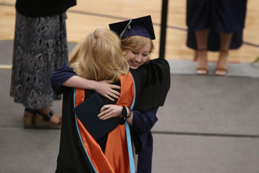 Holding both her mask and diploma, senior Jaclyn O'Hara hugs principal Gail Holder before walking across the stage.