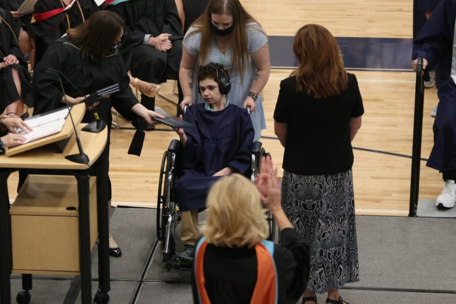 Rolling across the stage, senior Charlie Peters reaches out to grab his diploma.