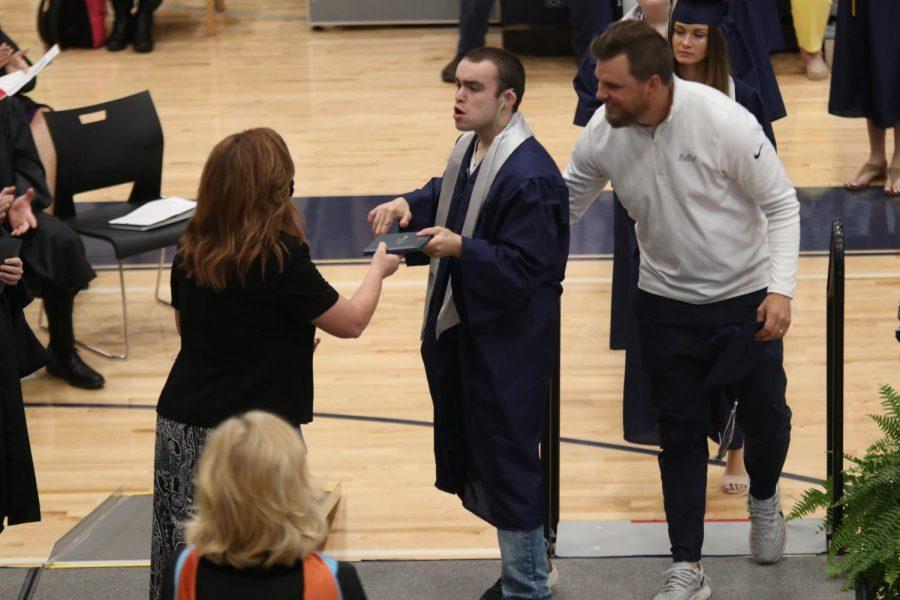 Walking across the stage, senior Rylan Rothgeb walks beside para Zach McFall as he grabs his diploma.