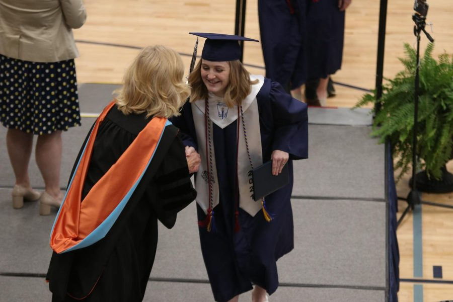 Leaning toward principal Gail Holder, senior Molly Smith smiles with her diploma in hand as she excitedly walks across stage.