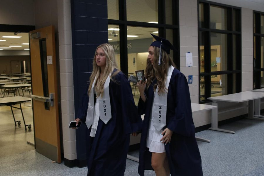 Walking down the main hallway for the last time, senior Avery Keopke and Alexa Marney look for places to take pictures.