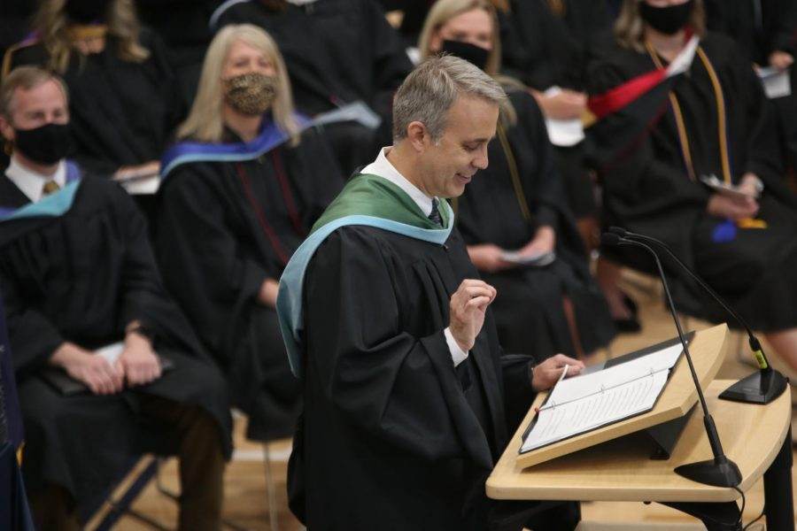 Laughing as he makes a joke, social studies teacher Jeff Wieland focuses on his paper as he addresses the senior class.
