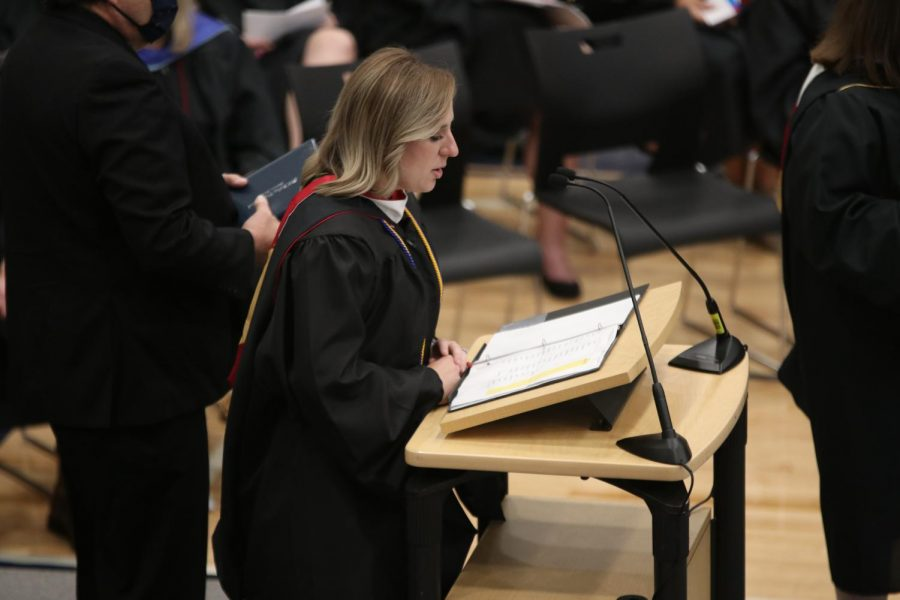 Focusing her eyes on the paper below, english teacher Page Anderson reads off names as the graduates walk by.