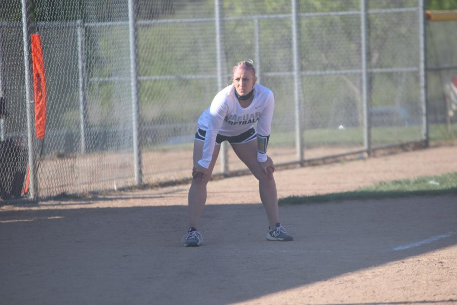 Crouching to watch the batter get into place, head coach Jessica DeWild stares intently.
