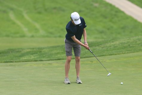 Paying close attention to the ball, junior Jack Dedrickson putts the golf ball.