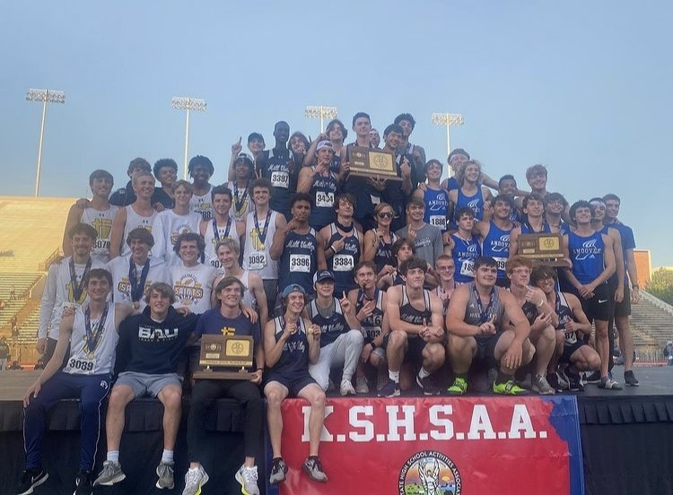 Throwing up the number one, the boys track team stand on the podium with their state championship trophy to commemorate winning the first state title in track and field in Mill Valley history.